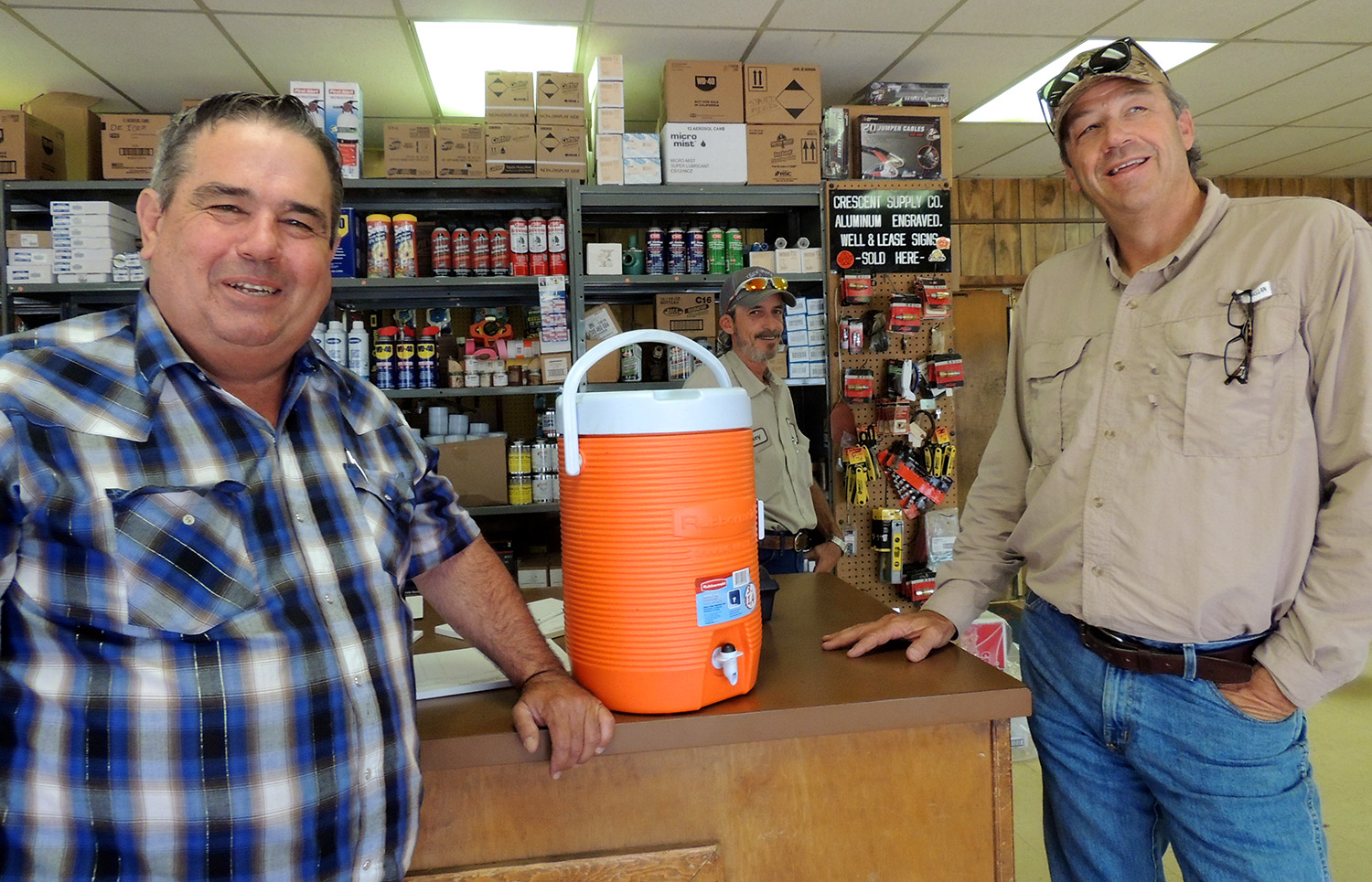 "The proverbial oilfield water can is worth a laugh amid the banter at Crescent Supply Co. in Abilene. ""If you ever drink out of that water can, it's like cocaine,"" said customer Derrell Riggan, right, referring to the addictive nature of working in the oil industry. ""You can't get off of it,"" said Scott Tarpley, Crescent manager. ""You're done."" Behind the counter is Rickey Weaver, assistant manager. Riggan owns DWR Oil Co. in Merkel. PHOTO BY HANABA MUNN WELCH"